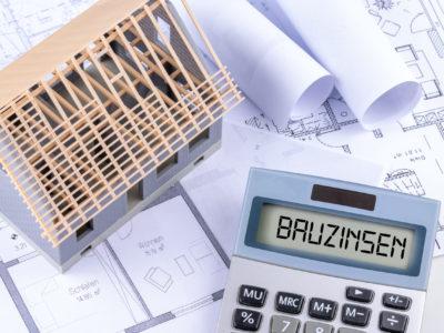 Taschenrechner mit dem Schlagwort Bauzinsen und einer Rohbau Immobilie mit Bauplänen als Hintergrund